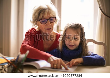Grandmother teaching to her granddaughter