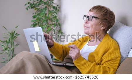 Grandmother Using Laptop Computer Relaxing In Bed. Computing Services for Retirees. Stock photo ©