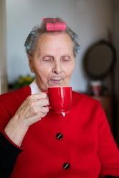 Grandmother with a smile is sitting at a table and drinking a coffee. The older woman has curlers on her head, and red blouse. Enjoying morning in her apartment. Portrait of old women