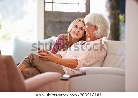 Grandmother With Adult Granddaughter Relaxing On Sofa Foto stock ©