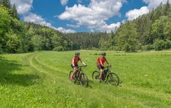 Grandmother with electric mountain bike and granddaughhter without electric help on a smooth meadow trail in the Franconian Switzerland area of Bavaria, Gemany