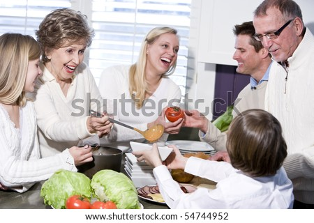 Grandmother with family cooking in kitchen, smiling and laughing together stock photo