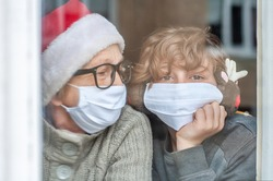 Grandmother with grandchild in a protective masks and Christmas hats are looking out misted window of house. Family leisure. Waiting for Christmas. Quarantin, isolated. Coronavirus covid-19. Stay home