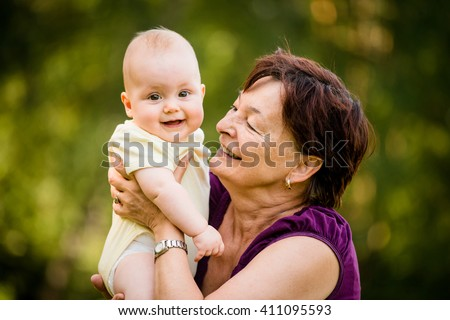 Grandmother with grandchild - senior woman holding her granddaughter outdoor in nature