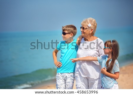 Grandmother with grandchildren having fun together on the seaside #458653996