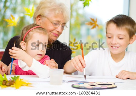 Grandmother with grandchildren painting with paintbrush and colorful paints, autumn background