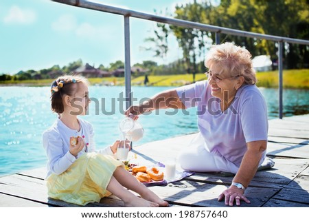 Grandmother with granddaughter eating breakfast on the lake