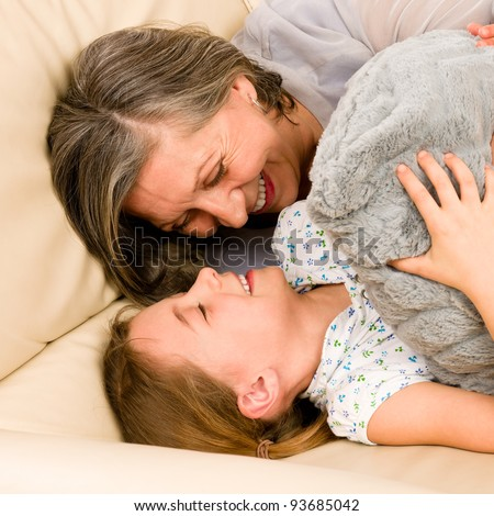 Grandmother with granddaughter hugging smiling together lying on sofa