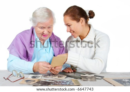 Grandmother with granddaughter looks old family photos.