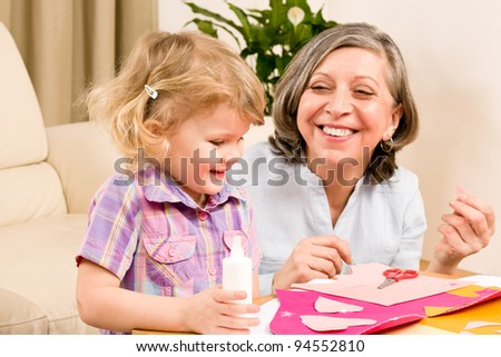 Grandmother with granddaughter playing together glue hearts on paper