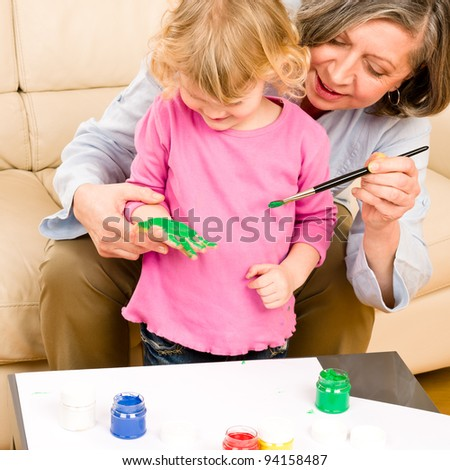 Grandmother with granddaughter playing together paint hand-prints on paper