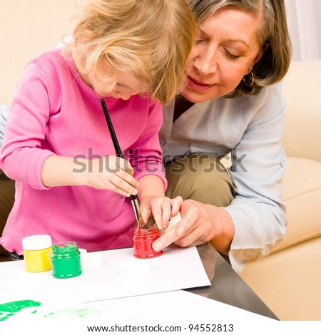 Grandmother with granddaughter playing together paint handprints on paper