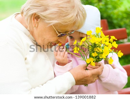 Grandmother with granddaughter sniffing yellow flowers in the park