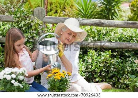 Grandmother with her granddaughter working in the garden