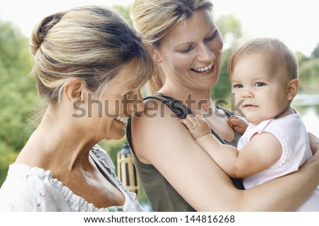 Grandmother with mother and daughter against the lake