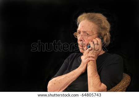 Grandmotherly woman hearing bad news on a cell phone