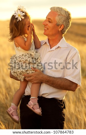 Grandpa hplding his crying baby girl on a wheat field. outdoor shot