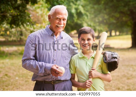 Grandpa spending time with grandson: Portrait of senior man playing baseball with his grandchild in park. The old man embraces the young kid holding the bat, smiling and looking at camera
