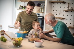 Grandpa you are the best cook. Grandfather his adult son and grandson together in  kitchen. lunch