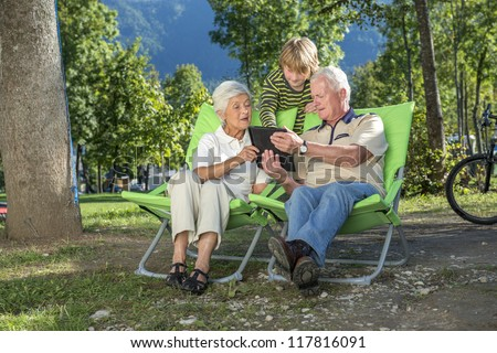 Grandparents and grandchild using their tablet computer while camping