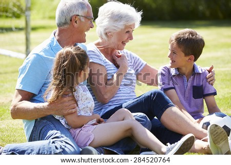 Grandparents And Grandchildren Playing Football In Garden