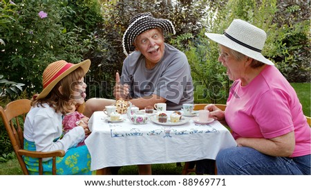Grandparents and granddaughter having a garden tea party and making funny faces at each other. Straw hats, china tea cups, cupcakes, and embroidered tablecloth are accessories. Horizontal format.