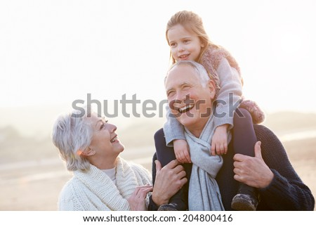 Grandparents And Granddaughter Walking On Winter Beach Foto stock ©
