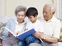 grandparents and grandson reading a book together.