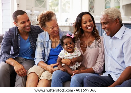 Grandparents and parents with a baby girl on mumâ??s knee