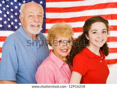 Grandparents and their granddaughter in front of an American Flag.