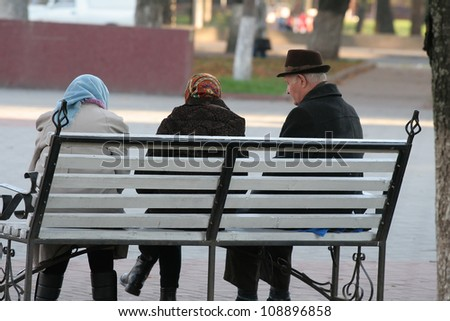 Grandparents are sitting on the bench - stock photo