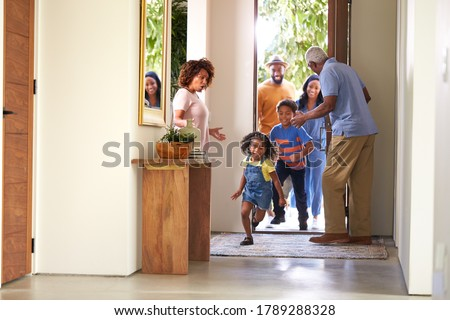 Grandparents At Home Opening Door To Visiting Family With Children Running Ahead Photo stock ©