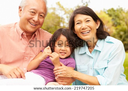 Grandparents Cuddling Granddaughter In Park #219747205