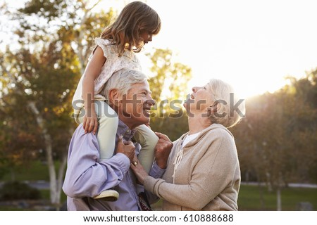 Grandparents Giving Granddaughter A Shoulder Ride In Park Сток-фото ©
