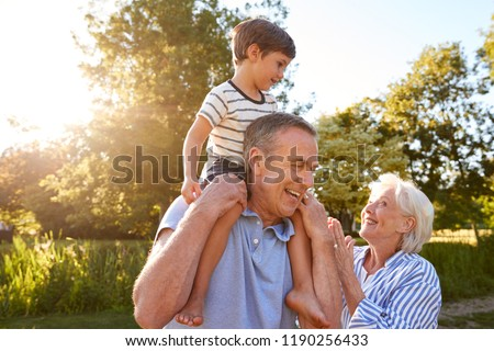 Grandparents Giving Grandson Ride On Shoulders In Summer Park Against Flaring Sun Сток-фото ©