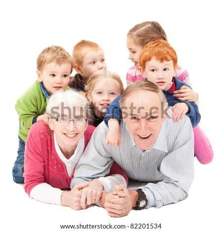 Grandparents lying on floor with grandchildren. Isolated on white.