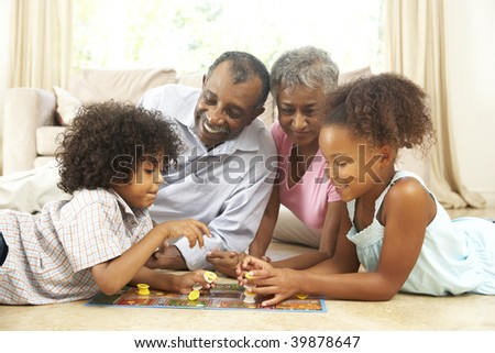 Grandparents Playing Board Game At Home With Grandchildren