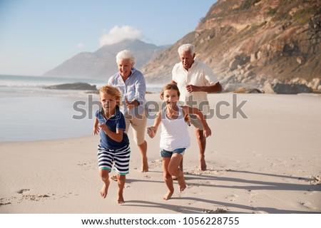 Grandparents Running Along Beach With Grandchildren On Summer Vacation