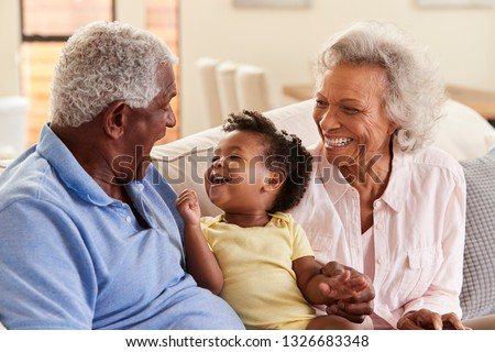 Grandparents Sitting On Sofa At Home Playing With Baby Granddaughter