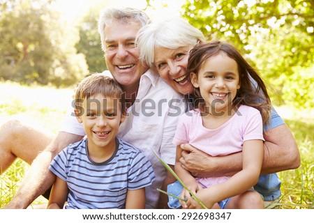 Grandparents sitting outdoors with their grandchildren