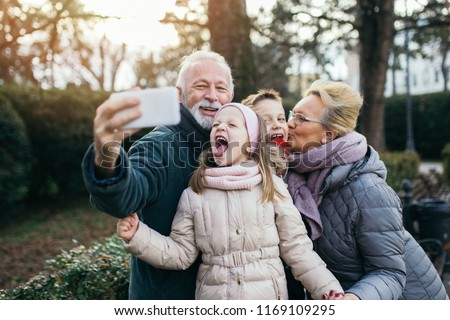 Grandparents taking selfie photo with their grandchildren in city park.  Сток-фото ©