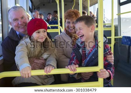 Grandparents taking their grandchildren out via the bus. The children are sitting on their grandparents knees.