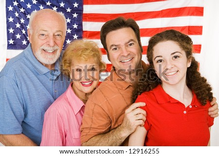 Grandparents, their adult child, and their granddaughter, posing in front of an American Flag.