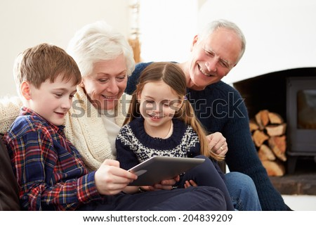 Grandparents Using Digital Tablet On Sofa With Grandchildren