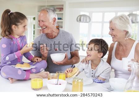 Grandparents With Grandchildren Eating Breakfast In Kitchen