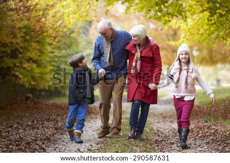 Grandparents With Grandchildren Walking Along Autumn Path