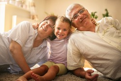 Grandparents with granddaughter at home.