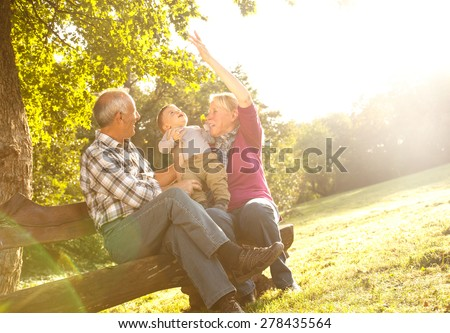 Grandparents with grandson enjoying the sunny autumn day in park