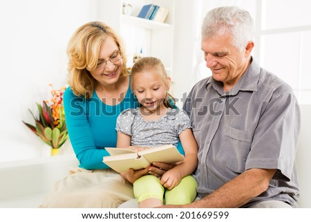 Grandparents with little girl reading book at home