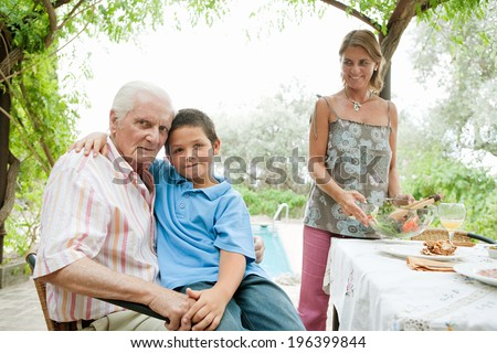 Grandson and grandfather sitting together at a healthy lunch table outdoors in a holiday villa green garden, smiling and relaxing by the swimming pool and eating healthy salad. Vacation lifestyle.